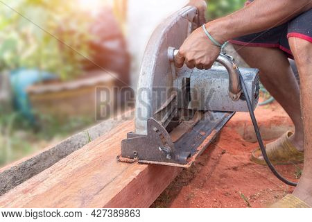 Building Contractor Worker Using Hand Held Worm Drive Circular Saw To Cut Boards On A New Home Const