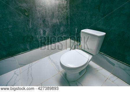 Ceramic White Toilet Bowl Near Grey Wall, Side Light In The Modern Bathroom. Modern Interior Of Rest