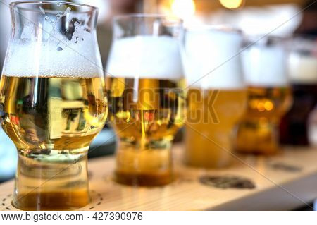 Brewery Tasting With Five Glasses Of Different Color And Opacity Of The Drink. Blurred And Indisting