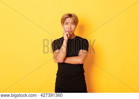 Upset Thoughtful Asian Guy Sulking And Looking Disappointed After Thinking, Standing Yellow Backgrou