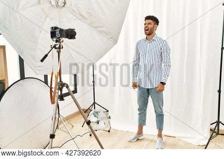 Arab young man posing as model at photography studio angry and mad screaming frustrated and furious, shouting with anger. rage and aggressive concept.