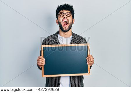 Young arab man with beard holding blackboard angry and mad screaming frustrated and furious, shouting with anger looking up.