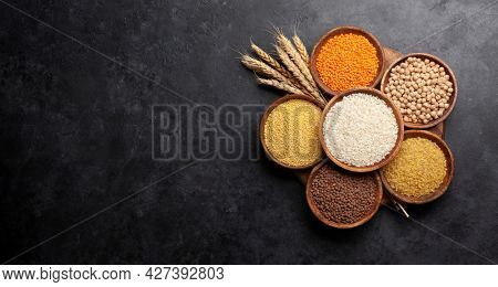 Gluten free cereals. Rice, buckwheat, corn groats, quinoa and millet in wooden bowls. Top view flat lay with copy space