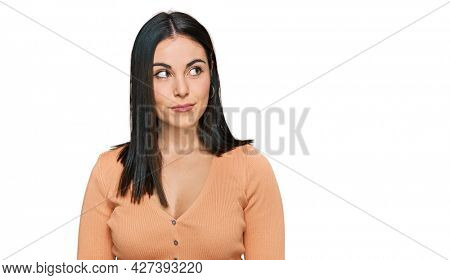 Young hispanic woman wearing casual clothes smiling looking to the side and staring away thinking.