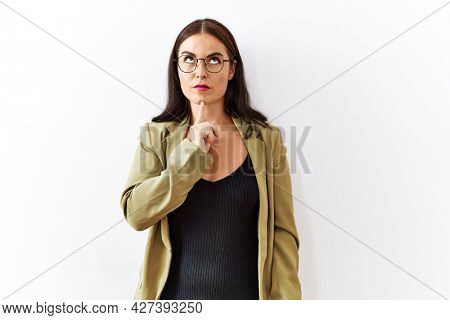 Young brunette woman standing over isolated background thinking concentrated about doubt with finger on chin and looking up wondering
