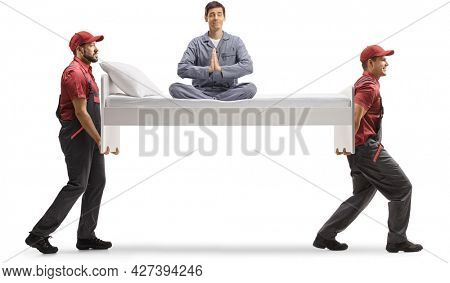 Movers carrying a single bed with man in pajamas sitting in a meditation pose isolated on white background
