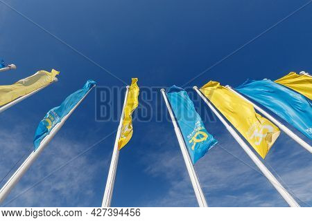 Almaty, Kazakhstan - July 02, 2021: Blue And Yellow Flags Against The Background Of A Clear Sky In H
