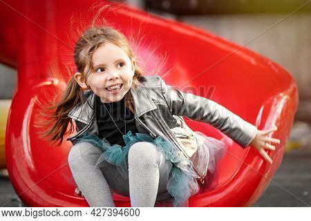 A Cheerful Girl Is Riding A Slide In The Park Playground And Laughing. Emotional Outdoor Portrait Of