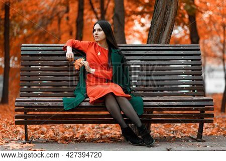 A Beautiful Young Woman Is Waiting For Her Boyfriend On A Bench In An Autumn Park. The Guy Is Late.
