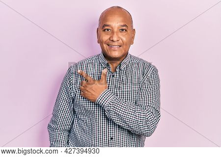 Middle age latin man wearing casual clothes cheerful with a smile of face pointing with hand and finger up to the side with happy and natural expression on face