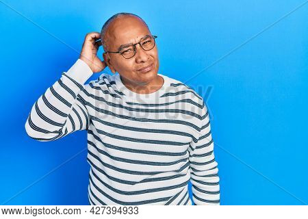 Middle age latin man wearing casual clothes and glasses confuse and wondering about question. uncertain with doubt, thinking with hand on head. pensive concept.