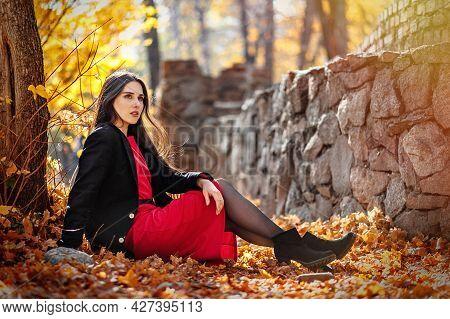Young Beautiful Woman Posing In Autumn Foliage Outdoor.