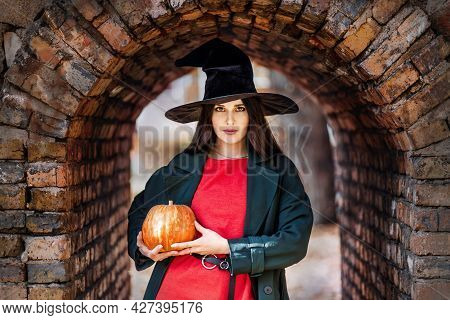 Pretty Young Woman Outdoor Portrait In Witch Hat Holding A Orange Pumpkin. Halloween Mood.