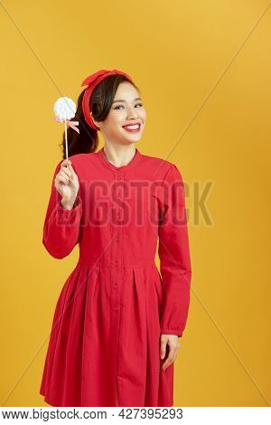 Fashion Asian Woman Holding Lollipop, Posing Against Yellow Background