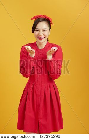 Young Asian Girl Over Isolated Yellow Background Holding Colorful French Macarons