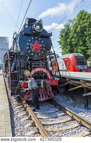 Worker Washes A Black Retro Steam Locomotive At The Railway Station