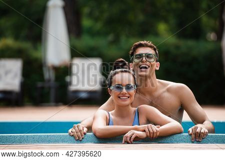Shirtless Man Standing Near Girlfriend In Swimming Pool During Vacation