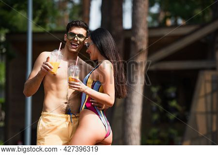 Shirtless Man With Orange Juice Hugging Girlfriend And Pointing With Finger On Resort
