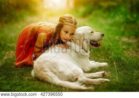 Cute little girl dressed in hippie style sits on the grass and hugs her beloved dog. Summertime. Kids and pets.