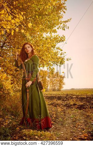 Historical reconstruction. Beautiful young woman archer with magnificent long red hair in a historical celtic dress stands on the edge of the forest.
