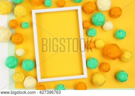 A White Empty Frame And A Lot Of Green And Yellow Balls Of Yarn For Knitting Or Crocheting On A Yell