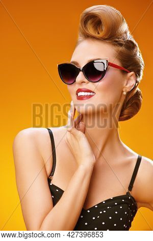 Portrait of a beautiful glamorous woman in elegant sunglasses. Pin-up style in clothes, hair and make-up. Yellow background.