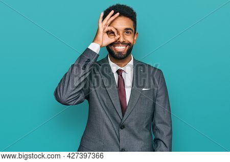 Young african american man wearing business clothes doing ok gesture with hand smiling, eye looking through fingers with happy face.