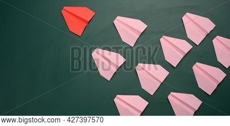 A Group Of Pink Paper Airplanes Follow The First Red Airplane Against A Green Background. The Concep