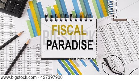 Closeup A Notebook With Text Fiscal Paradise , Business Concept Image On The Chart Background