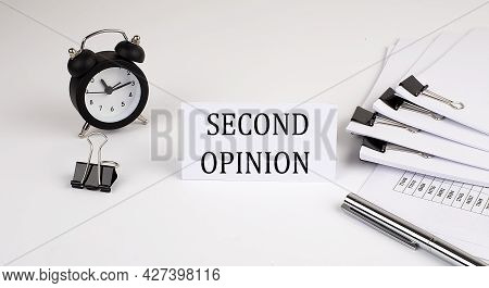 Card With Text Second Opinion On A White Background, Near Office Supplies And Alarm Clock. Business