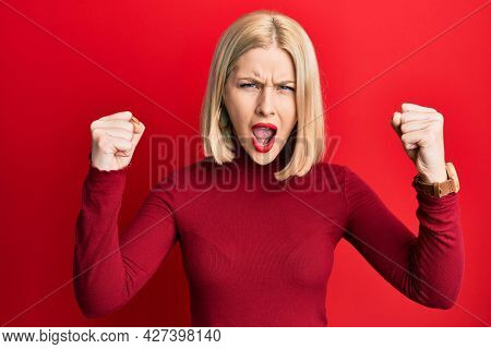 Young blonde woman wearing casual clothes angry and mad raising fists frustrated and furious while shouting with anger. rage and aggressive concept.