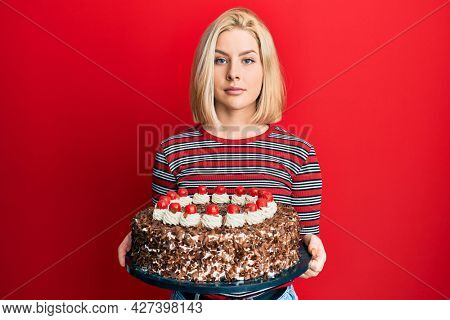Young blonde woman celebrating birthday holding big chocolate cake relaxed with serious expression on face. simple and natural looking at the camera.