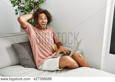 Young hispanic man sitting on the sofa at home using laptop crazy and scared with hands on head, afraid and surprised of shock with open mouth