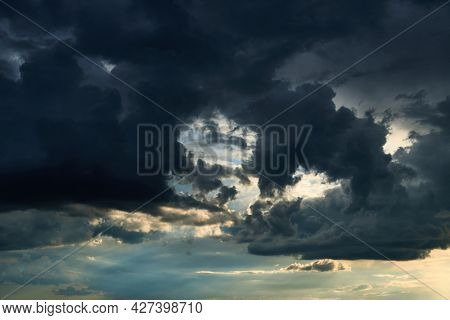 beautiful dark dramatic sky with sunlight and clouds as a background