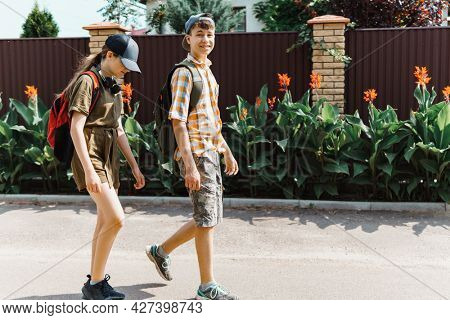 two teenagers boy and girl going down the street to school, education and back to school concept