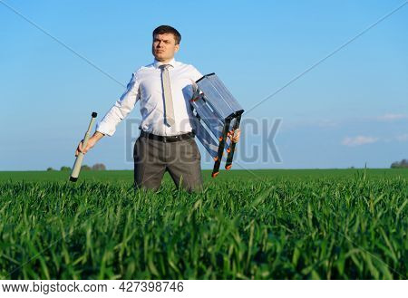 businessman poses with a spyglass in a green field, he looks an idea or something, business concept, green grass and blue sky as background