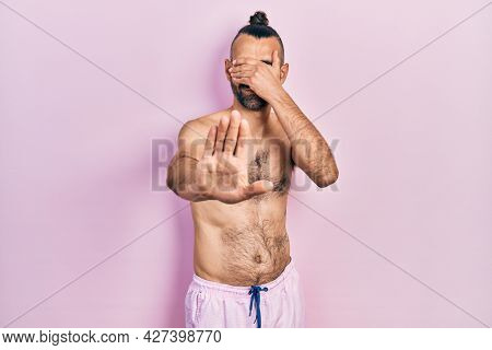 Young hispanic man shirtless wearing swimsuit covering eyes with hands and doing stop gesture with sad and fear expression. embarrassed and negative concept.