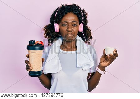 Young african american woman wearing sport clothes drinking a protein shake depressed and worry for distress, crying angry and afraid. sad expression.