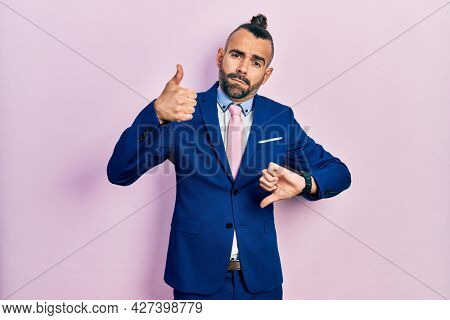 Young hispanic man wearing business suit and tie doing thumbs up and down, disagreement and agreement expression. crazy conflict