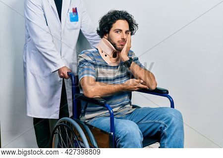 Handsome hispanic man sitting on wheelchair wearing neck collar thinking looking tired and bored with depression problems with crossed arms.