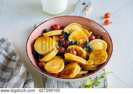 Mini Pancakes With Gooseberries And Blueberries In A Pink Bowl On A Light Background. American Cuisi