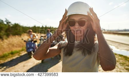 Portrait Of Young African American Woman Putting On Helmet For Driving Scooter On Road Outdoors In W