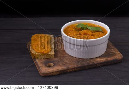 A Dish With Squash Caviar And A Black Bread Sandwich With Squash Caviar On A Wooden Board. Squash Sp