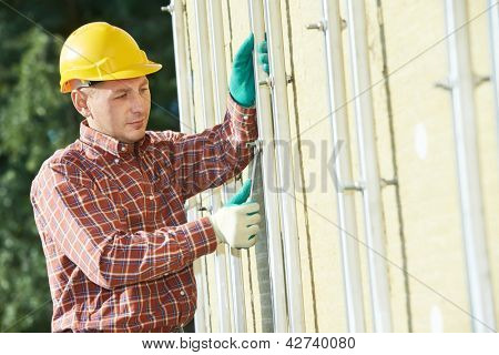 worker builder installing ventilated facade metal construction of building for granite tile
