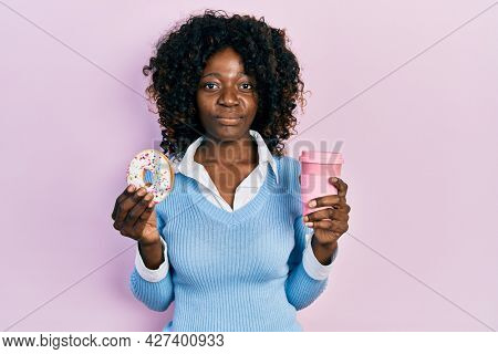 Young african american woman eating doughnut and drinking coffee relaxed with serious expression on face. simple and natural looking at the camera.