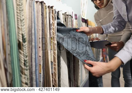 Seller And Buyer Choose Fabrics For Curtains In Showroom