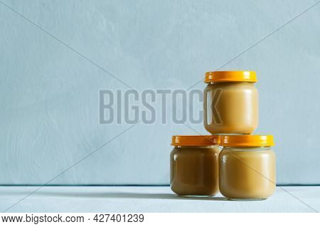 Three Jars Of Vegetable Zucchini Puree Or Fruit Apple Sauce. Baby Food On Grey Background. Copy Spac