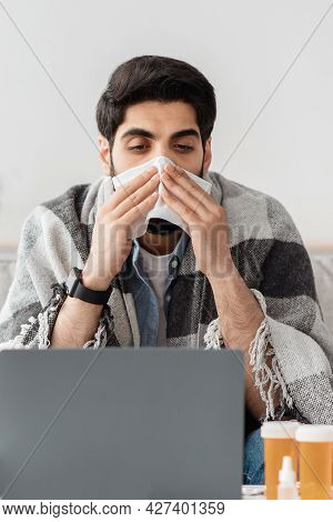 Remote Work. Ill Arab Guy Having Rhinitis Sneezing And Blowing Runny Nose, Working On Laptop At Home