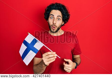 Handsome hispanic man holding finland flag scared and amazed with open mouth for surprise, disbelief face