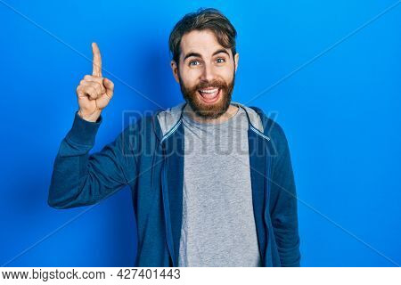 Caucasian man with beard wearing casual sweatshirt pointing finger up with successful idea. exited and happy. number one.